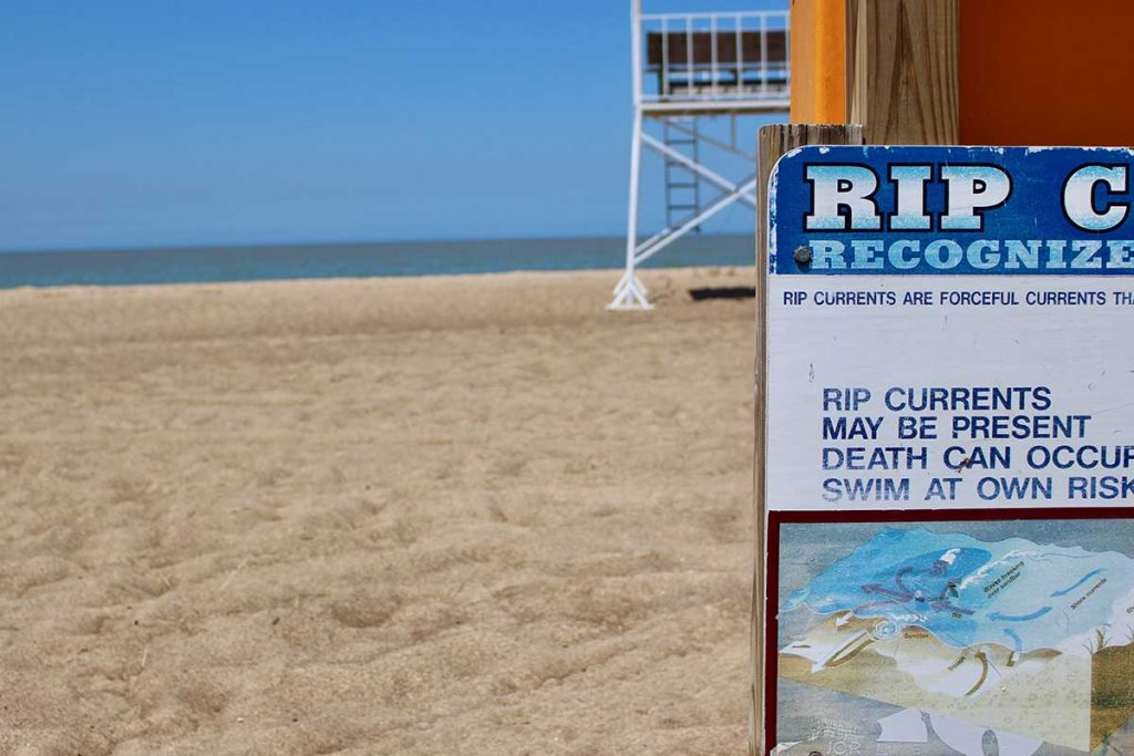 A sign warning of rip currents at New Buffalo Lakefront Park and Beach. (Bridge photo by Jim Malewitz)