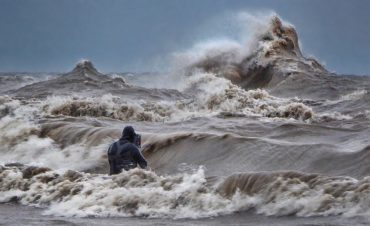 Photographer, Dave Sandford stands in the water to capture waves on Lake Erie. CREDIT DAVID HINTON