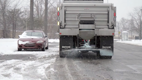 A truck spreading salt during a snow fall