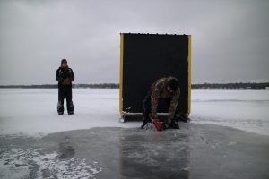 Ice fisherman preparing to fish for lake sturgeon on Black Lake in Michigan. Photo courtesy of Great Lakes Today